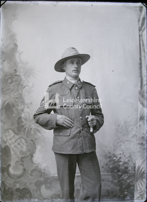 Young man posing in studio, with cane and cavalry hat
