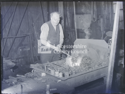 Blacksmith holding iron bar over furnace