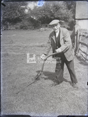 Elderly man standing with scythe